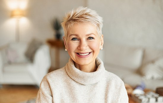 Older woman in sweater smiling with dental crowns in Houston, TX