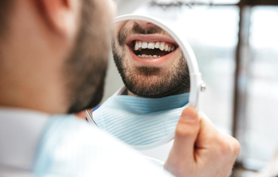 Man smiling while looking in dental mirror